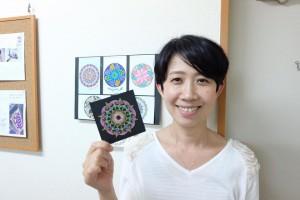 曼荼羅アートを持つ田村さん